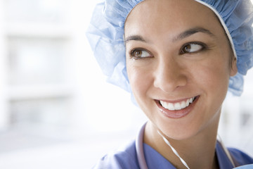 Young female nurse wearing hygiene cap, smiling, close-up