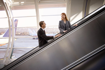 Businesswoman and businessman looking at each other on escalator in airport, smiling, side view