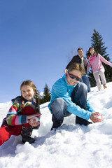 Boy and girl (7-9) making snow balls in snow field, smiling, portrait, couple smiling in background