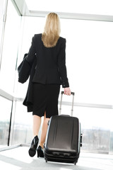 Businesswoman traveling, pulling suitcase along inside station or airport