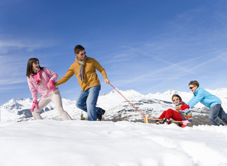 Couple pulling daughter and son (7-9) in sled on snow, smiling, side view, mountain range in background