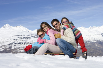 Couple with daughter and son (7-9) on sled in snow, wearing sunglasses, smiling, portrait