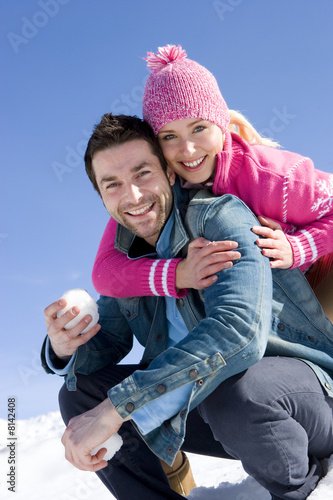 Young couple embracing in snow, man holding snow ball, smiling, portrait