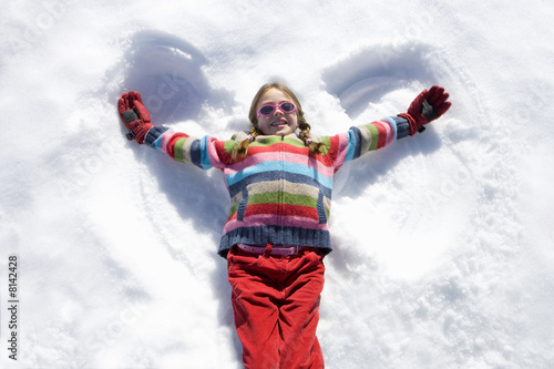 Girl (7-9) lying in snow making 'angel wings', smiling, overhead view