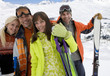 Two young couples with skis in snow, smiling, portrait