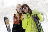 Two young women with skis in snow, wearing sunglasses, smiling, portrait