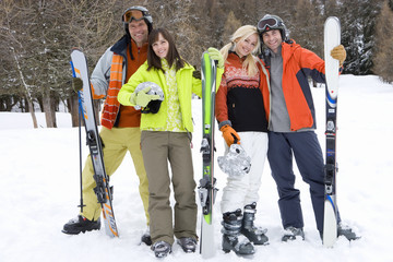 Two young couples standing with skis in snow, smiling, portrait