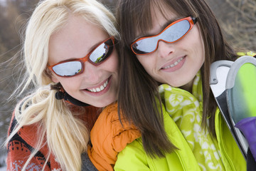 Two young women with skis in snow, wearing sunglasses, smiling, portrait, close-up
