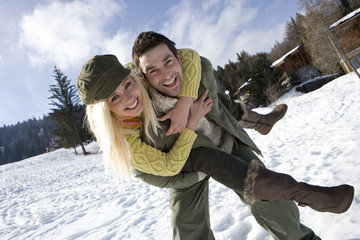 Young couple embracing outdoors in snow, smiling, portrait