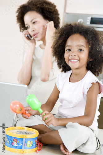 Little girl playing toy drum while mother tries to talk on the telephone