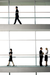 Office workers walking around modern office building