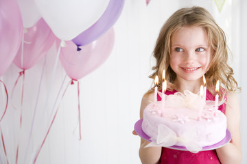 happy little girl holding birthday cake