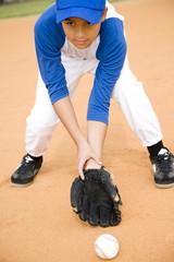 Boy stooping to pick up baseball
