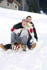 Young couple riding sled down snow slope, smiling, portrait, low angle view