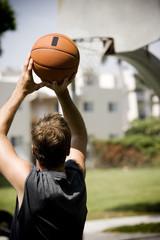 man shooting hoops on an urban basketball court