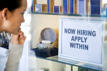 Woman looking at job advert in shop window