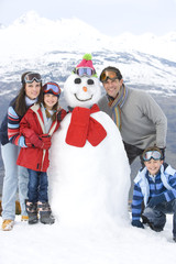 Family of four standing by snowman in snow, smiling, portrait, mountain range in background