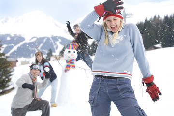 Two young couples having snow fight in snow, smiling