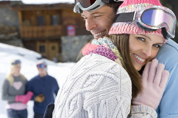 Young couple embracing in snow field, smiling, friends smiling in background