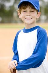 Portrait young boy on baseball pitch
