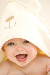 Baby girl (9-12 months) smiling, wearing towel on head, close-up