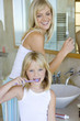 Mother and daughter (6-8) brushing their teeth in bathroom, smiling, portrait of girl