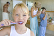Girl (6-8) brushing her teeth in bathroom, portrait, family in background