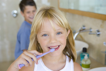 Boy and girl (6-8) brushing their teeth in bathroom, smiling, portrait, girl in foreground