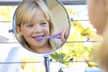 Girl (6-8) brushing teeth in bathroom, looking at reflection in mirror