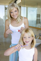 Mother and daughter (6-8) holding toothbrushes in bathroom, smiling, portrait