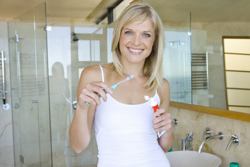 Young woman holding toothbrush in bathroom, smiling, portrait