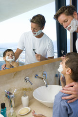 Father and son (6-8) shaving in bathroom, smiling