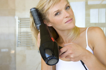 Young woman blow drying hair in bathroom, portrait, close-up