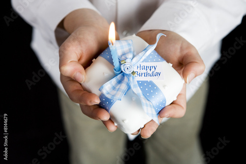 close up shot hands holding miniature birthday cake