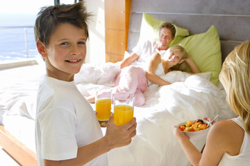 Boy and girl (6-8) bringing breakfast to parents embracing in bed, smiling