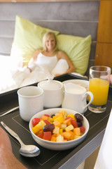 Man holding tray of breakfast by young woman smiling in bed