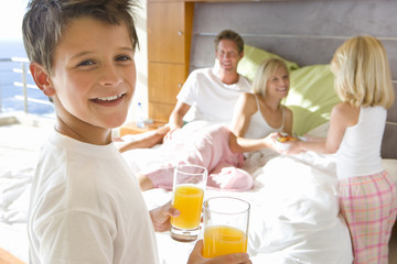 Boy and girl (6-8) bringing breakfast to parents in bed, smiling, portrait of boy