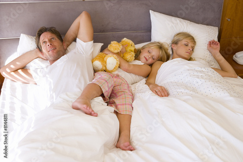 Daughter(6-8) lying in bed between parents, man looking up at ceiling