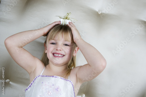 Little girl holding a present on top of her head
