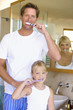 Couple and daughter (6-8) brushing their teeth in bathroom, smiling, portrait