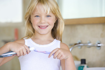 Girl (6-8) applying toothpaste on toothbrush in bathroom, smiling, portrait