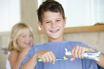 Boy (6-8) applying toothpaste on toothbrush in bathroom, smiling, portrait, sister brushing teeth in background