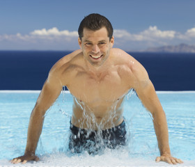 A man emerging from a swimming pool