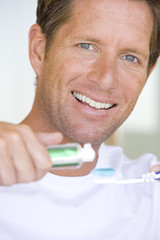 Man applying toothpaste on toothbrush, smiling, portrait, close-up