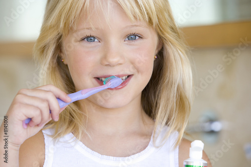 Girl (6-8) brushing teeth in bathroom, smiling, portrait, close-up