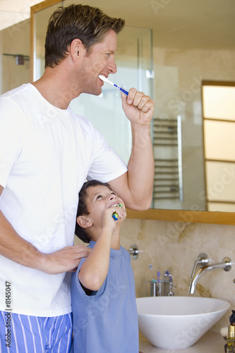 Father and son (6-8) brushing their teeth in bathroom, smiling