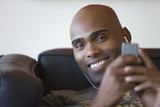 Young man listening to mp3 player on sofa, smiling, portrait, close-up
