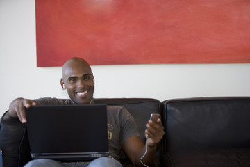 Young man holding mp3 player and using laptop on sofa, smiling, portrait
