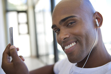 Young man holding mp3 player,  smiling, portrait, close-up