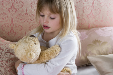 Young girl in her bedroom hugging a teddy bear